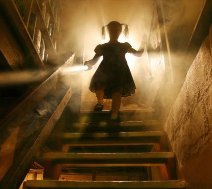 Girl walking down dark stairs.